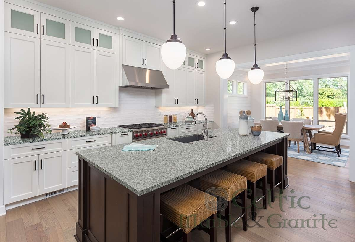 beautiful kitchen in new luxury home with island, pendant lights, and hardwood floors. Includes view of dining room.